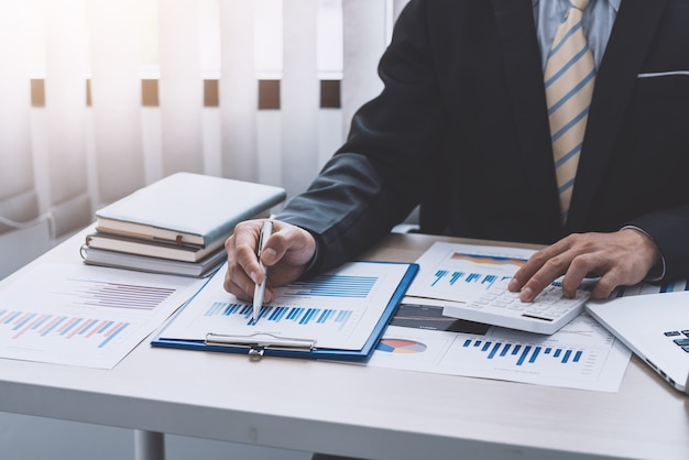 Primo piano di una mano di uomo d'affari che tiene una penna che punta a un grafico utilizzando una calcolatrice per calcolare in ufficio.