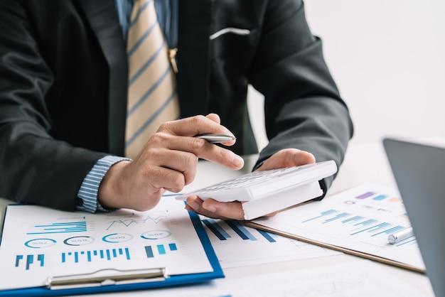 Primo piano di una mano dell'uomo d'affari che tiene una penna con un foglio grafico del calcolatore di documenti collocato in ufficio.