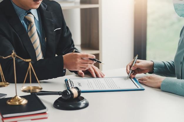 Primo piano di una mano di uomo d'affari che indica un documento a un cliente che tiene una penna per firmare documenti contrattuali in ufficio.