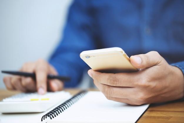 Chiudere la mano di uomo d'affari utilizzando la calcolatrice e scrivere in un notebook conteggio prendendo appunti contabilità a fare finanze in ufficio. concetto di finanze di risparmio.