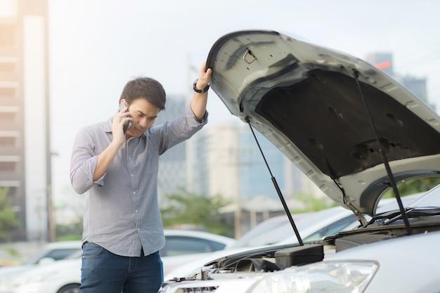 Chiudere la mano dell'uomo d'affari utilizzando uno smartphone mobile chiamare un meccanico per chiedere aiuto assistenza perché l'auto si è rotta.