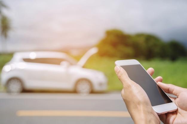 Chiudere la mano dell'uomo d'affari utilizzando uno smartphone mobile chiamare un meccanico di automobili per chiedere assistenza