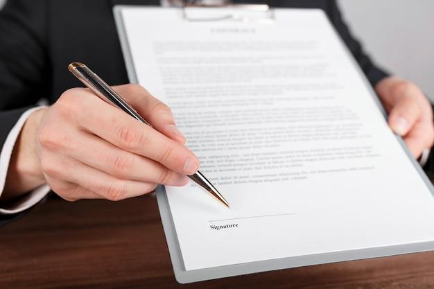 Primo piano di un uomo d'affari che consegna un contratto, allegato a un blocco per appunti per la firma