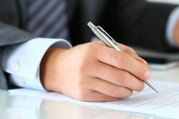 Chiuda in su delle mani dell'uomo d'affari che firmano i documenti. uomo che scrive qualcosa seduto nel suo ufficio. accordo di partenariato di firma del contatto, saldo di chiusura o creazione di un concetto di relazione finanziaria