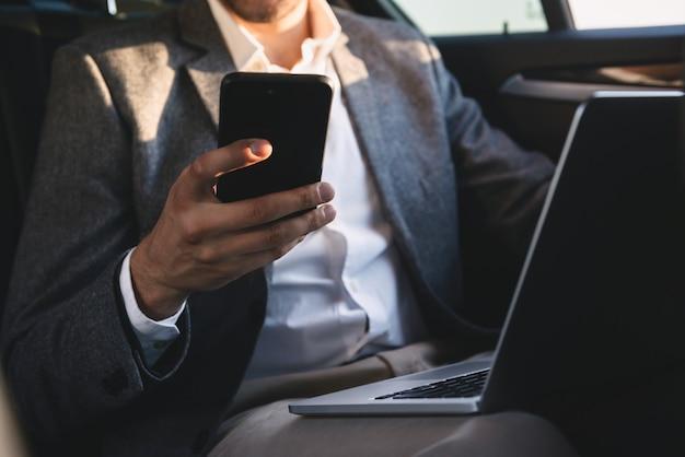 Chiuda in su del telefono mobile della holding dell'uomo d'affari