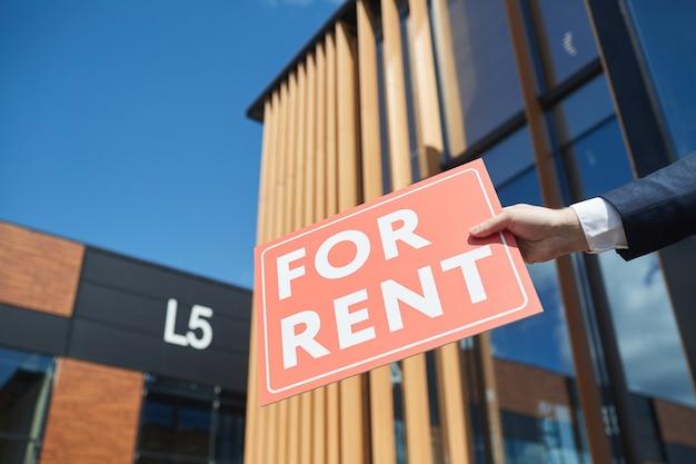 Primo piano dell'uomo d'affari che tiene il cartello in affitto contro il nuovo edificio per uffici moderno