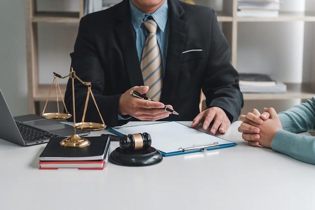 Primo piano dell'avvocato e del cliente dell'uomo d'affari che si siedono all'ufficio che negoziano insieme facendo uso del documento.