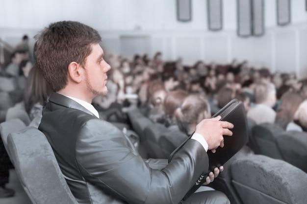 Primo piano.uomo d'affari che ascolta l'altoparlante nella sala conferenze. affari e istruzione