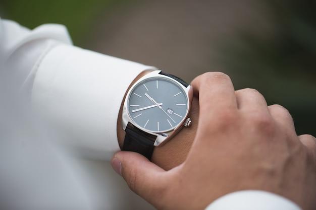 Chiuda in su dell'uomo d'affari guardando l'orologio sulla sua mano all'aperto, spazio libero