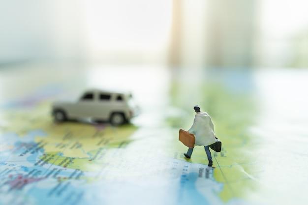 Chiuda su della figura miniatura dell'uomo d'affari con la valigia della borsa che funziona sulla mappa di mondo variopinta alla mini automobile bianca con lo spazio della copia.