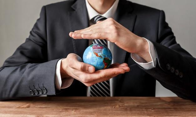 Primo piano di uomo d'affari che protegge il globo del mondo