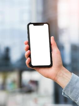 Primo piano del telefono cellulare della tenuta della mano dell'uomo d'affari con la visualizzazione di schermo bianca