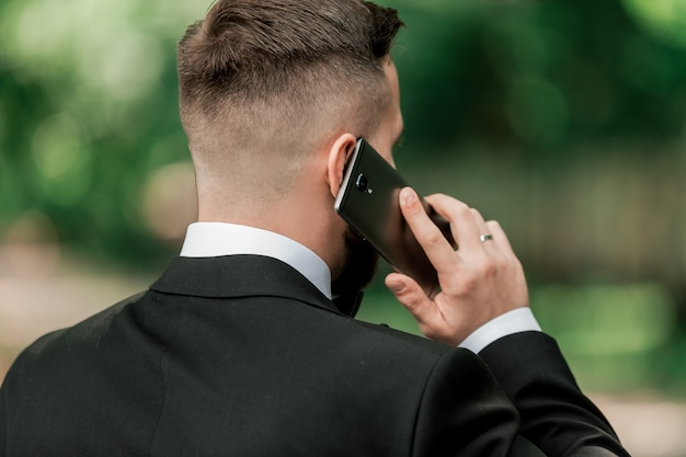 Avvicinamento. uomo d'affari parlando sul suo smartphone su una strada cittadina