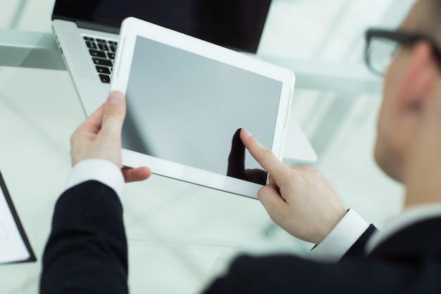Avvicinamento. uomo d'affari che tocca lo schermo della tavoletta digitale. persone e tecnologia