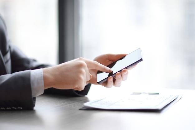 Avvicinamento. imprenditore digitando su uno smartphone, seduto alla scrivania.