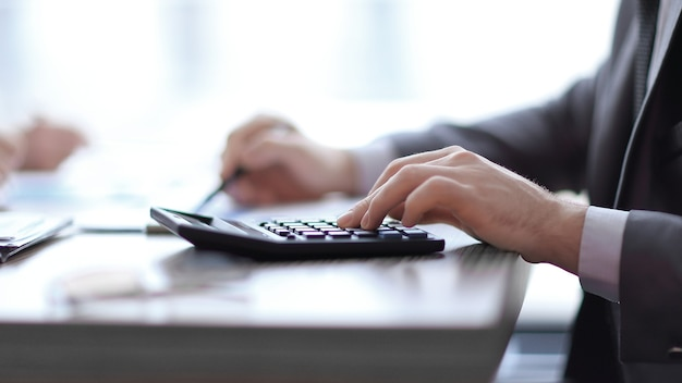 Avvicinamento. l'uomo d'affari usa la calcolatrice seduto dietro una scrivania.
