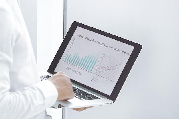 Avvicinamento. un uomo d'affari usa un laptop per lavorare con i dati finanziari. concetto di business
