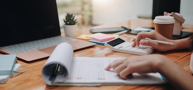 Primo piano uomo d'affari che utilizza calcolatrice e laptop per calcolare finanza, tasse, contabilità, statistiche e concetto di ricerca analitica