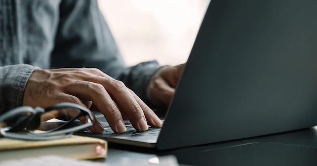 Chiuda sull'uomo d'affari che per mezzo del computer portatile