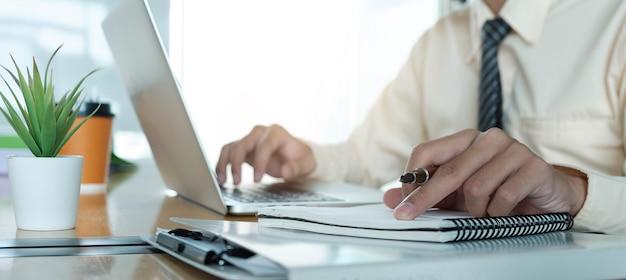 Primo piano dell'uomo d'affari che utilizza il computer portatile per fare finanza matematica sulla scrivania in legno in ufficio e sfondo di lavoro aziendale, tasse, contabilità, statistiche e concetto di ricerca analitica
