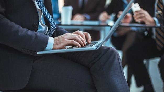 Avvicinamento. uomo d'affari utilizzando laptop in ufficio. persone e tecnologia