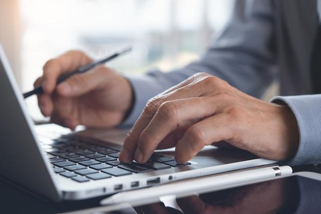 Chiuda in su dell'uomo d'affari che lavora al computer portatile sul tavolo dell'ufficio
