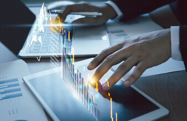 Primo piano uomo d'affari che lavora sul ponte dell'ufficio da tavolo per la crescita del business o il mercato azionario con le statistiche dei dati a livello di grafico o grafico. concetto finanziario e tecnologico, icona di pianificazione e strategia.