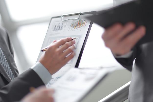 Chiuda sull'uomo d'affari che lavora con i dati del grafico in ufficio.