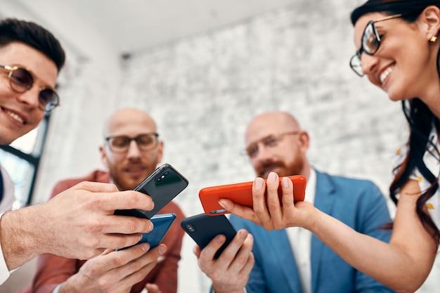 Close up di imprenditori e imprenditrici utilizzando smart phone, concetto di business.