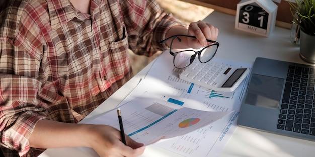 Primo piano di una donna d'affari o di un contabile che tiene in mano la penna che lavora sulla calcolatrice per calcolare i dati aziendali, il documento contabile e il computer portatile in ufficio, il concetto di business