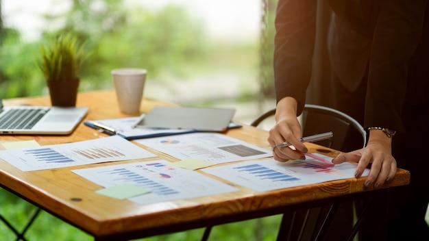 Primo piano di una donna d'affari che analizza su documenti di dati finanziari sulla scrivania pensando a un'idea per risolvere il problema
