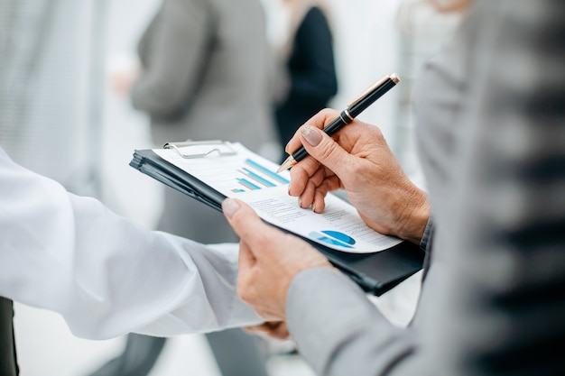 Chiuda sulla donna di affari che controlla il concetto di affari del documento finanziario