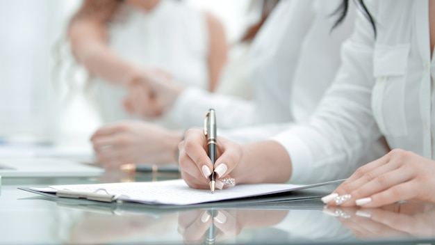 Donna di affari del primo piano che riempie il modulo sul colloquio di lavoro