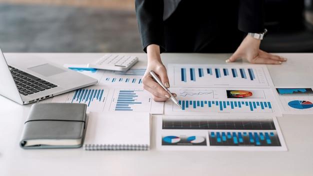 Primo piano di una penna della tenuta della mano della donna di affari che indica ad un grafico disposto su una tavola dell'ufficio.