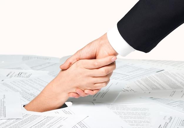 Primo piano della mano della donna d'affari in una pila di documenti