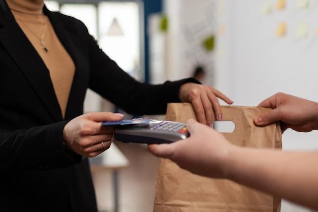 Primo piano della mano della donna d'affari utilizzando la carta di credito credit