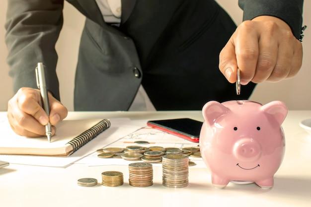 Primo piano di una donna d'affari che tiene una moneta in un salvadanaio, un concetto di risparmio di denaro per la contabilità finanziaria.