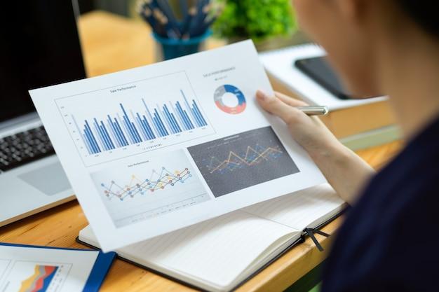 Primo piano della donna d'affari che tiene, guardando i rapporti sulle prestazioni di vendita in ufficio