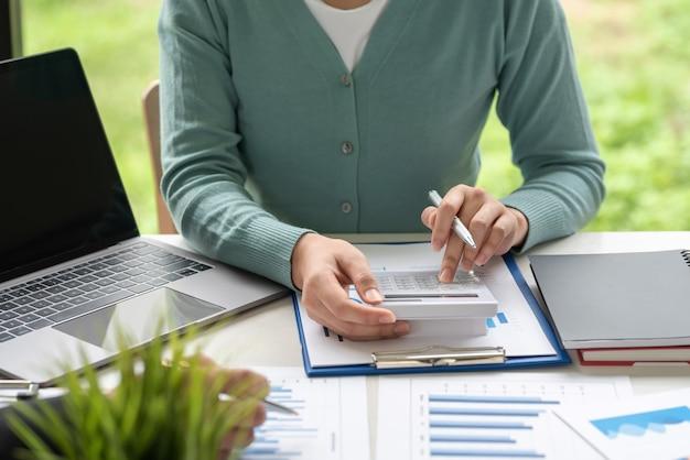 Donna di affari del primo piano che tiene una penna usando la calcolatrice per calcolare contabilità, statistiche e concetti di lavoro in ufficio.