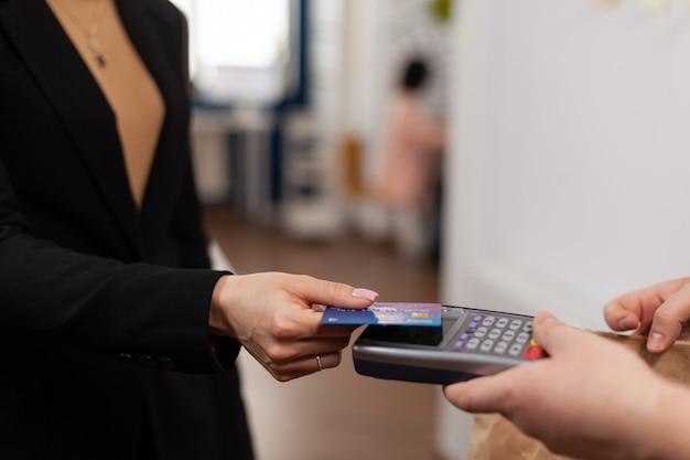 Primo piano di una donna d'affari che tiene in mano una carta di credito in plastica, che paga la consegna del cibo nell'ufficio dell'azienda. utilizzo del pagamento senza contatto per il cibo da asporto. portare un pasto gustoso.