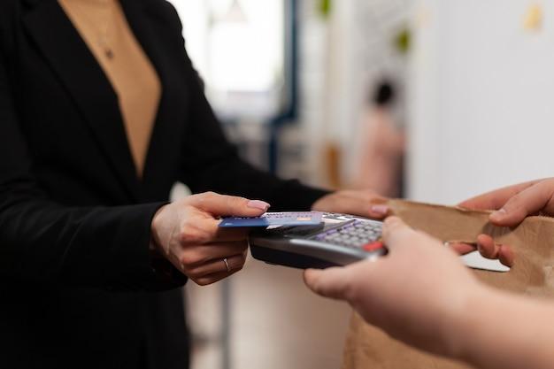 Primo piano di una donna d'affari che tiene in mano una carta di credito in plastica che paga per la consegna del cibo in azienda