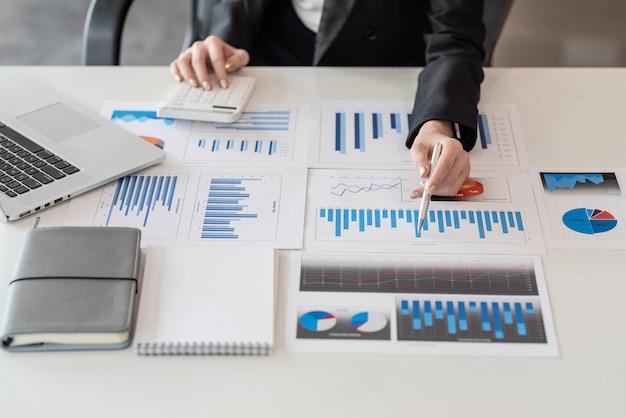 Primo piano di una donna d'affari che punta a un grafico con una calcolatrice in ufficio.