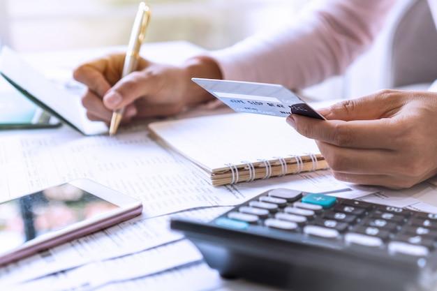 Chiuda sulla donna di affari che prende nota delle spese domestiche al suo scrittorio con il calcolatore dal suo lato, concetto di spese familiari.