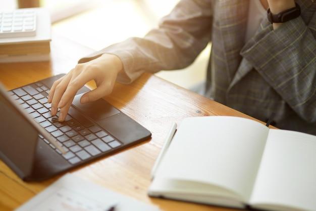 Primo piano, donna d'affari che digita sulla tastiera portatile del tablet con un taccuino vuoto sulla scrivania da lavoro