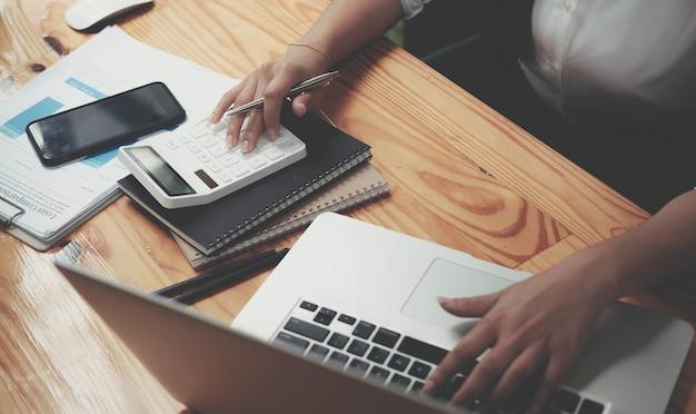 Primo piano imprenditrice che utilizza calcolatrice e laptop per calcolare finanza, tasse, contabilità, statistiche e concetto di ricerca analitica