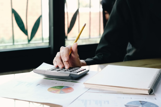 Close up imprenditrice utilizzando calcolatrice e laptop per fare matematica matematica sulla scrivania in legno in ufficio e affari, tasse, contabilità, statistiche e concetto di ricerca analitica