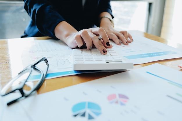 Close up imprenditrice utilizzando calcolatrice e laptop per fare matematica matematica sulla scrivania di legno in ufficio e business di lavoro sullo sfondo, tasse, contabilità, statistiche e concetto di ricerca analitica