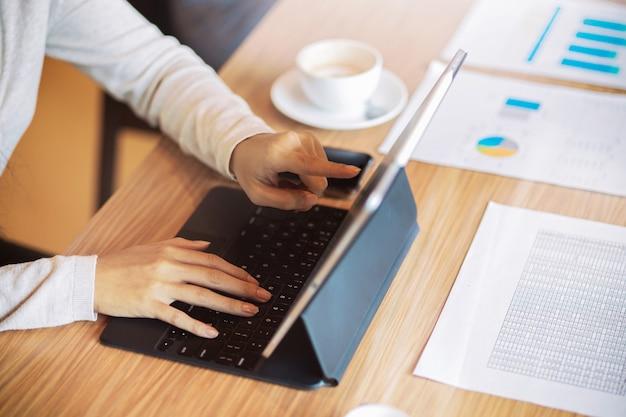 Donna d'affari ravvicinata che utilizza, cerca, naviga, tocca la tavoletta digitale in una riunione finanziaria