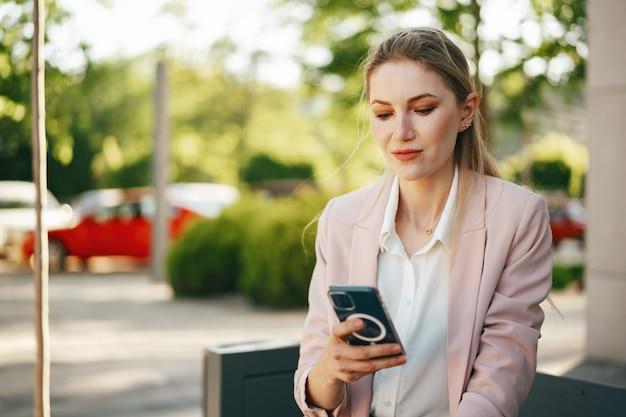 Primo piano di una donna d'affari che utilizza lo smartphone all'aperto in città