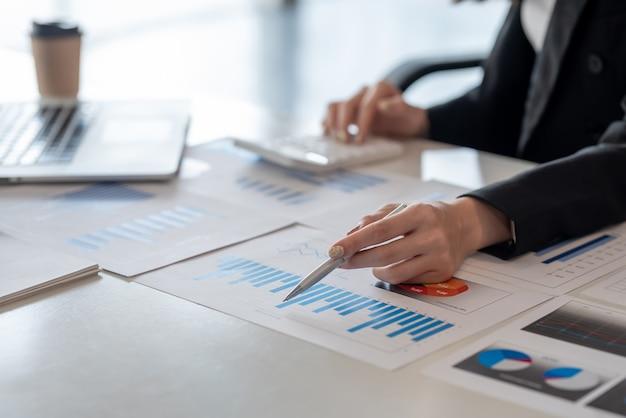 Avvicinamento. analisi di lavoro della donna di affari che indica il grafico all'ufficio.